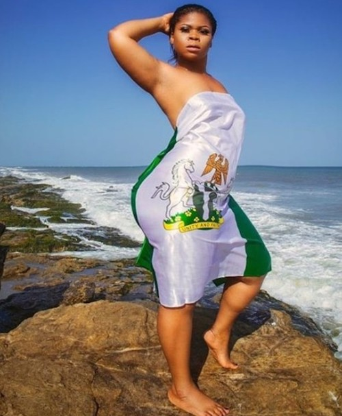 Nigerian girl covers body with flag