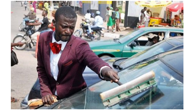 Man in suit spotted cleaning car windscreens