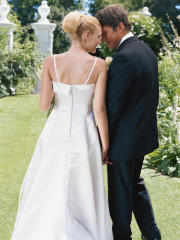 Newlywed couple walking together holding hands on lawn, rear view